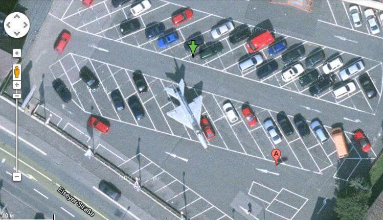 истребитель, припаркованный на стоянке автомобилей